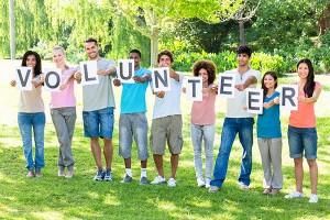 Teens holding sign: Volunteer