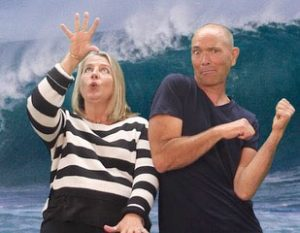 Woman and man in front of wave
